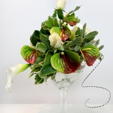 Arrangement of white roses, cala lillies and antheriums.