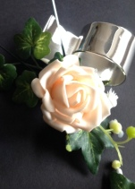 Buttonholes and corsages, pictured here peach roses and lily of the valley