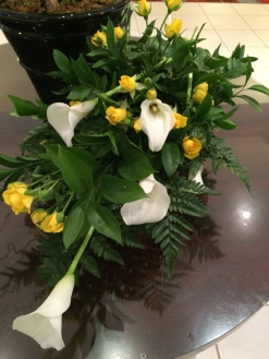 Cala lilies and roses in a willow trug