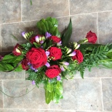Picture of red rose in cross shape on tiled floor