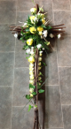 Rustic cross based with moss and willow twigs. Pictured here with a cluster of roses and spray carnations. Price available on request.