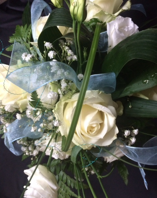 Close up of ribbons and white and cream roses