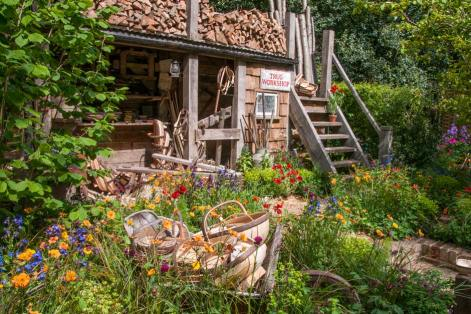 Trugs on display amongst flowers and trug maker's shed