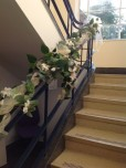 White flowers and greenery decorating staircase